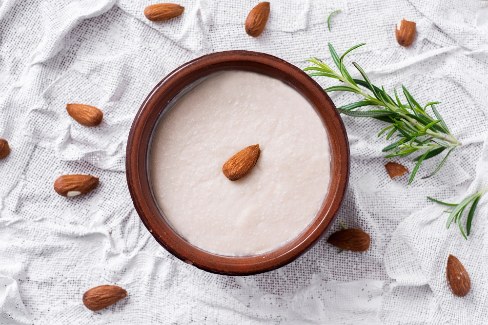 2ATP1TD high angle view of an earthenware bowl with menjar blanc, a dessert made with almonds and sugar typical of Catalonia, Spain, on a white textured surfa